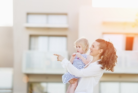 Happy mother with baby standing in front of house building and pointing on copy space photo