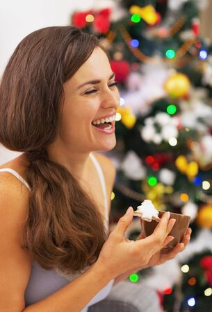 Happy young woman in pajamas having snack near christmas tree photo