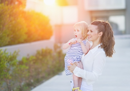 Happy mother and baby in front of house building looking on copy space photo