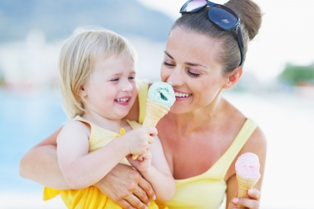 Smiling baby giving mother ice cream photo