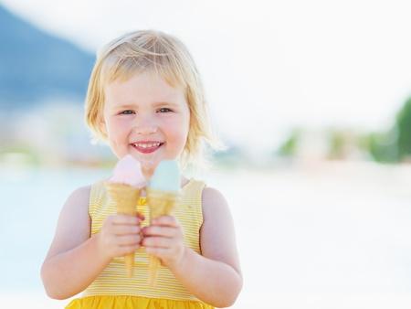 Glimlachende baby die twee roomijshoornen eet