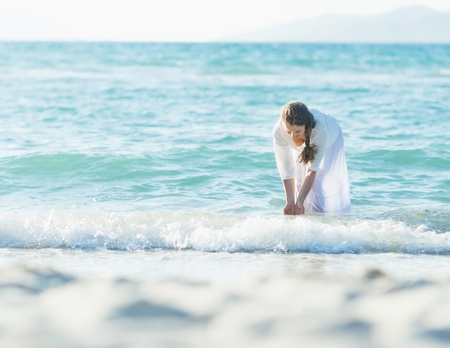 wetting: Happy young woman wetting hands in sea