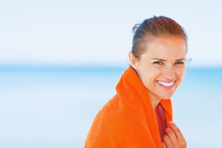 beach wrap: Portrait of smiling young woman wrapped in towel on beach