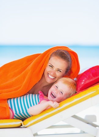 beach wrap: Portrait of smiling mother and baby laying on sunbed