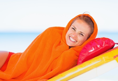 beach wrap: Smiling young woman wrapped in towel laying on sunbed Stock Photo