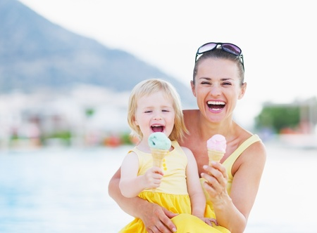 Happy mother and baby eating ice cream
