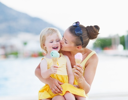 woman with ice cream: Mother kissing baby while eating ice cream Stock Photo