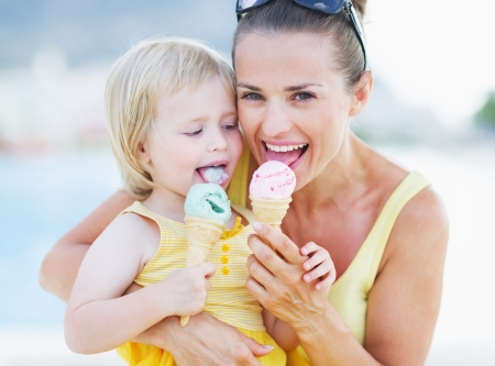 Happy mother and baby eating ice cream photo