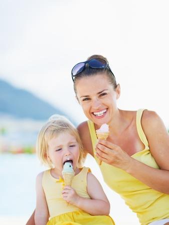 eating ice cream: Sonriendo madre y el beb� que come el helado Foto de archivo