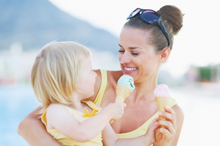 ice cream woman: Smeared mother and baby eating ice cream