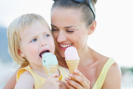 Portrait of happy mother and baby eating ice cream photo