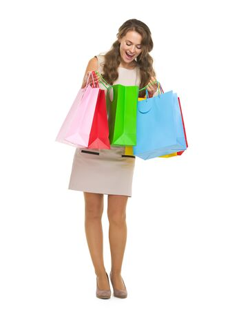 Full length portrait of happy young woman checking shopping bags photo