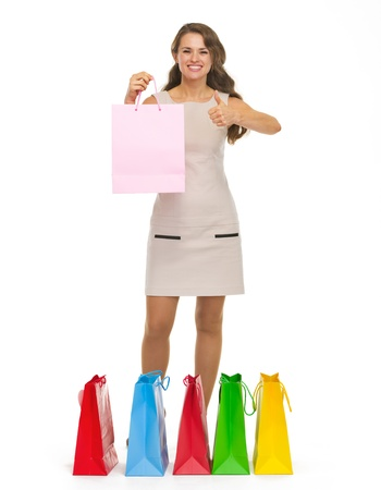 Full length portrait of happy young woman showing shopping bags and thumbs up photo