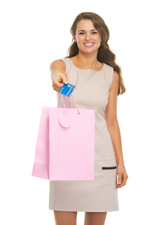 Smiling young woman showing shopping bag and credit card Stock Photo - 21354932
