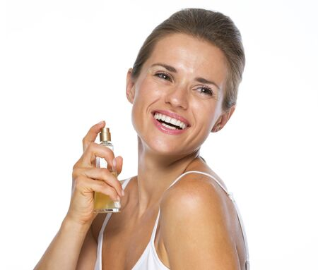 Happy young woman applying perfume photo