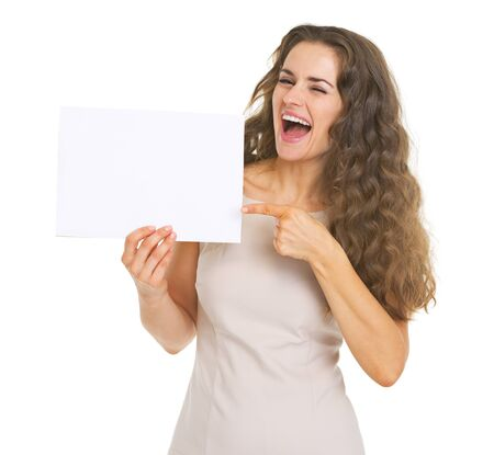 Smiling young woman pointing on blank paper sheet Stock Photo - 21359605