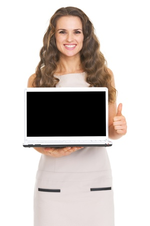 Happy young woman showing laptop blank screen showing thumbs up photo