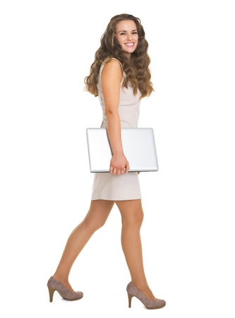 topicality: Full length portrait of young woman with laptop going sideways