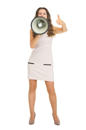 Full length portrait of young woman shouting through megaphone and showing thumbs up Stock Photo - 21359631