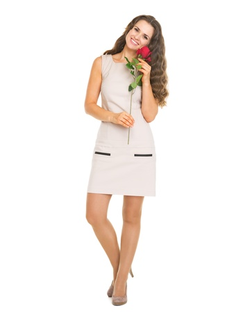 Full length portrait of happy young woman holding red rose photo
