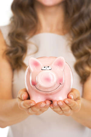 Closeup on piggy bank in hand of young woman Stock Photo - 21338320