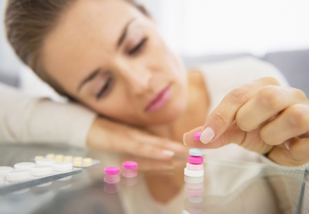 Closeup on frustrated young woman playing with pills Stock Photo - 21359694