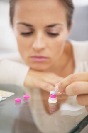 Closeup on stressed young woman playing with pills Stock Photo - 21359695