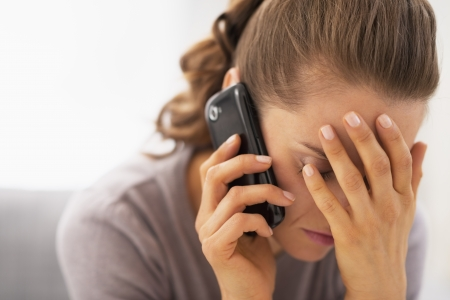 home phone: Stressed young woman talking mobile phone