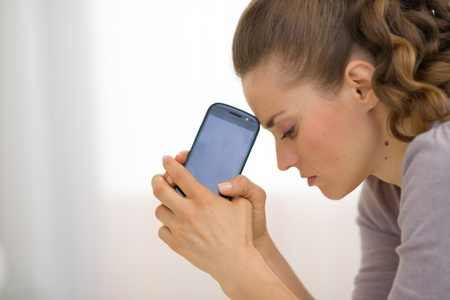 Portrait of stressed young woman with cell phone Stock Photo - 21359706