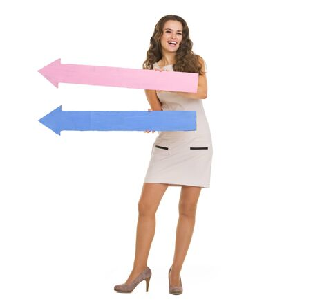 Happy young woman with arrows pointing in one way Stock Photo - 21359738