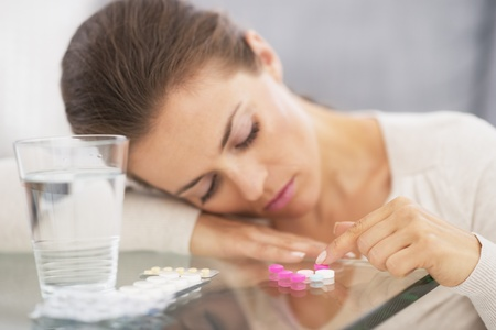 Closeup on stressed young woman playing with pills photo