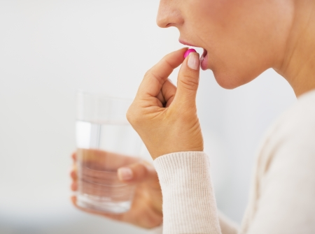pills in hand: Closeup on young woman eating pill