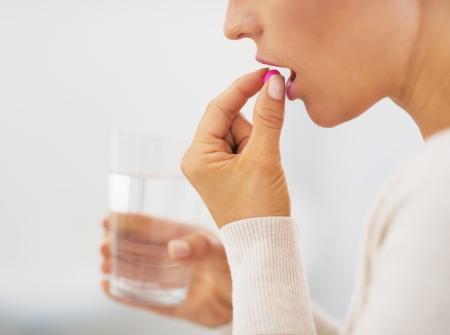 pastillas: Primer plano de mujer joven que come la p�ldora