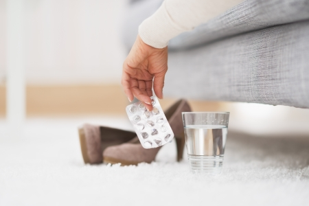 Closeup on empty medicine blister package in hand of young woman laying on couch Stock Photo - 21341849
