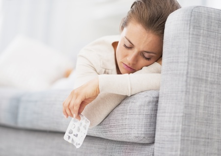 Young woman laying on sofa and holding empty medicine blister package Stock Photo - 21359729