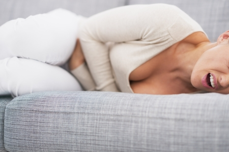 Closeup on feeling bad young woman laying on sofa photo