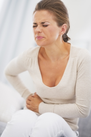 Young woman having stomach pain Stock Photo - 21359740
