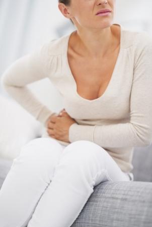 dolor abdominal: Primer plano de mujer joven que tiene dolor de estómago