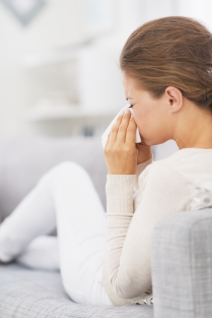 Woman sitting on couch and blowing nose into handkerchief