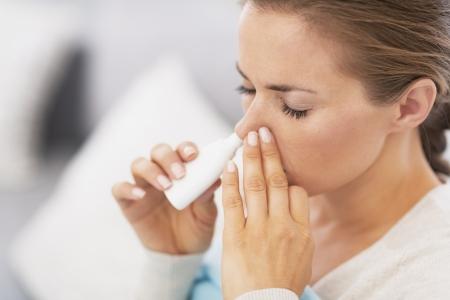 Vrouw met behulp van neusdruppels Stockfoto