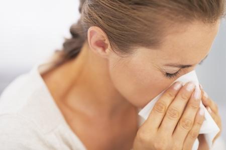 rheum: Woman blowing nose into handkerchief