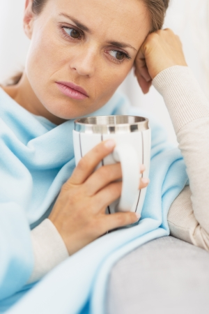 Ill woman with cup of hot beverage Stock Photo - 21359753