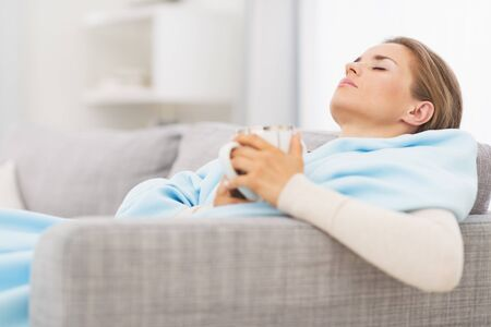 Ill woman with cup of hot beverage sitting on couch Stock Photo - 21359754