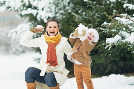 snow woman: Happy mother and baby throwing snowballs in winter park Stock Photo