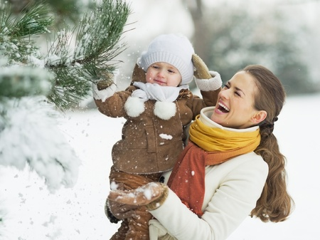 kids playing outside: Happy mother and baby playing with snow on branch Stock Photo