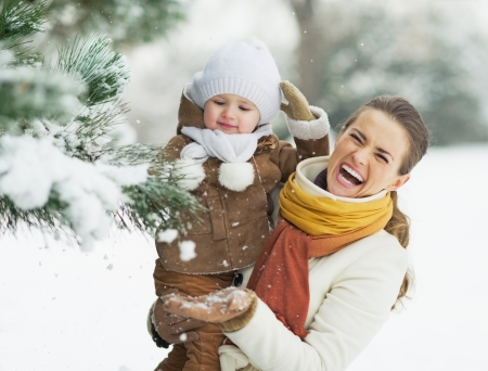 winter woman: Happy mother and baby playing with snow on branch Stock Photo