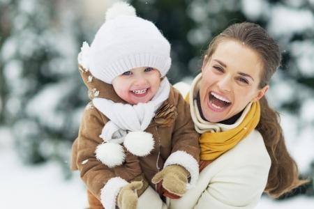 Portret van gelukkige moeder en baby in de winter park Stockfoto