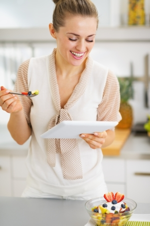 Smiling young housewife eating fruits salad and using tablet pc photo