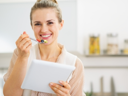 Happy young housewife with tablet pc eating fruits salad photo
