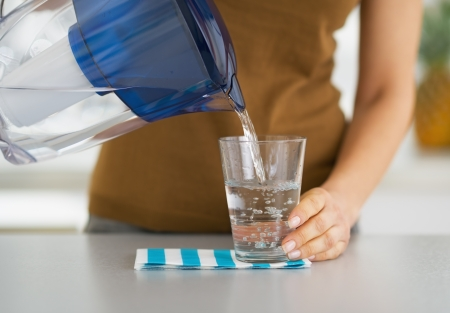 Closeup on housewife pouring water into glass from water filter pitcher photo